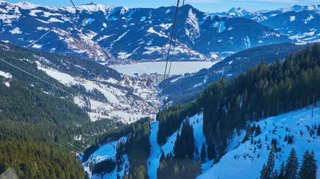 ski run : ZELL AM SEE, AUSTRIA - FEBRUARY 28, 2019: Schmittenhohenbahn cable car breath-taking journey with a view on Alpine snowy slopes, pistes, forests and frozen Zeller see, on February 28 in Zell Am See