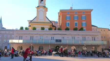 mozart : SALZBURG, AUSTRIA - FEBRUARY 27, 2019: The outdoor restaurant in crowded Mozart square (Mozarplatz) with a view on belfry of St Michael church (Michaelskirche), on February 27 in Salzburg.