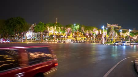siamês : BANGKOK, THAILAND - MAY 1, 2019: Time lapse of the speed traffic in evening Ratchadamnoen Avenue, lined with trees, covered with lighting garlands, on May 1 in Bangkok Stock Footage