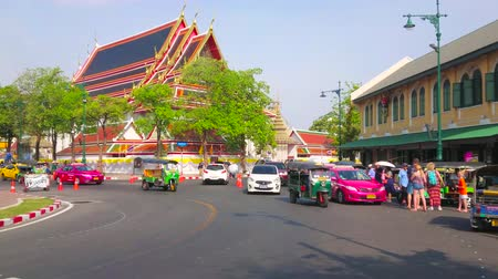 wat pho : BANGKOK, THAILAND - APRIL 22, 2019: The speed traffic in Maha Rat Road with a view on tourist stores, cafes and roof of Wat Pho Buddhist Temple, on April 22 in Bangkok