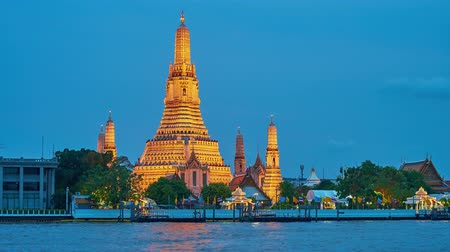 кхмерский : BANGKOK, THAILAND - APRIL 22, 2019: The view on Thonburi bank of Chao Phraya river with splendid medieval Wat Arun Temple in bright evening illumination, on April 22 in Bangkok Стоковые видеозаписи