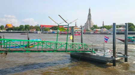 siamês : BANGKOK, THAILAND - APRIL 22, 2019: The view on bobbing pontoon pier on Chao Phraya river, floating boats, ferries and Wat Arun Temple on the background, on April 22 in Bangkok