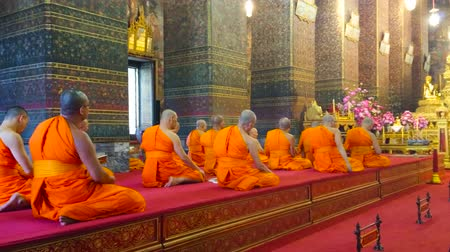 phra : BANGKOK, THAILAND - APRIL 22, 2019: The bhikkhu monks pray during the worship in Phra Ubosot of Wat Pho Buddhist complex, on April 22 in Bangkok