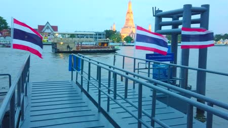 кхмерский : BANGKOK, THAILAND - APRIL 22, 2019: The view on Wat Arun Temple in evening lights behind the Chao Phraya river with floating ships, barges and pontoon pier with flags, on April 22 in Bangkok