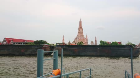 кхмерский : BANGKOK, THAILAND - APRIL 22, 2019: Watch the day activity on Chao Phraya river with floating ferries, ships and boat, dragging barges along the Wat Arun Temple, on April 22 in Bangkok