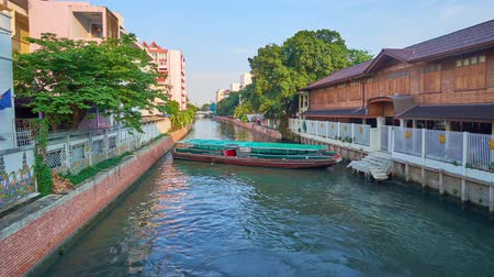 épületek : BANGKOK, THAILAND - APRIL 24, 2019: The long ferry boat makes the complex turn in the narrow Saensaeb canal at its terminal station, on April 24 in Bangkok