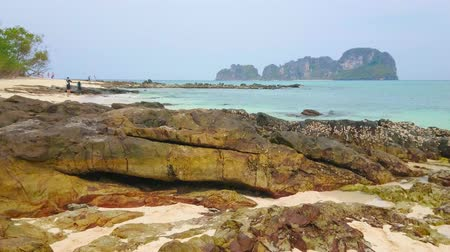 aonang : The rocks on the sandy Bamboo beach of Ko Mai Phai (Bamboo Island) with a view on the azure waters of Andaman sea and Ko Yung Island on background, Ao Nang, Krabi, Thailand