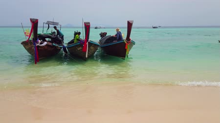 bobbing : AO NANG, THAILAND - APRIL 27, 2019: The longtail boats are rocking on the gentle waves at the white sand shore of Bamboo Island (Ko Mai Phai), on April 27 in Ao Nang Stock Footage