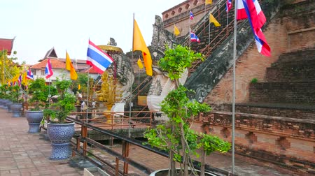 Чеди : CHIANG MAI, THAILAND - MAY 2, 2019: Walk around the medieval brick ruins of Wat Chedi Luang Buddhist Temple, surrounded by waving flags and plants in pots, on May 2 in Chiang Mai