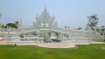 rebirth : CHIANG RAI, THAILAND - MAY 9, 2019: Unique architecture of modern White Temple (Wat Rongkhun) with bridge of rebirth cycle and Gate of Heaven, covered with relief patterns, on May 9 in Chiang Rai