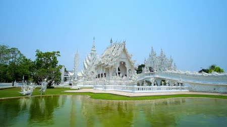 rebirth : CHIANG RAI, THAILAND - MAY 9, 2019: Exterior of White Temple (Wat Rongkhun) with ornate bridge of rebirth cycle across a lake, Gate of Heaven and splendid Ubosot (main hall), on May 9 in Chiang Rai