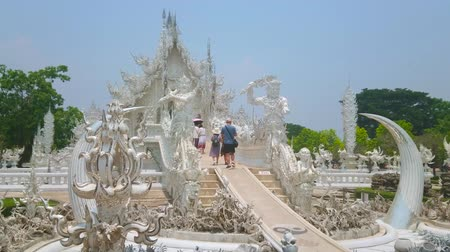rebirth : CHIANG RAI, THAILAND - MAY 9, 2019: Tourists enter the bridge of rebirth cycle of White Temple (Wat Rongkhun), guarded by giant Kinnaree guards, on May 9 in Chiang Rai