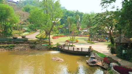 siamês : The perfectly landscaped Mae Fah Luang (Doi Tung) botanical garden with small lake, surrounded by lush green trees and flower beds, Chiang Rai, Thailand