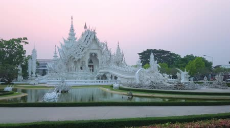 rebirth : The splendid White Temple (Wat Rongkhun) with its ornate bridge, sculptures, statues, mirror patterns, relief decors and a small lake on twilight, Chiang Rai, Thailand Stock Footage