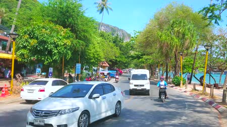 aonang : AO NANG, THAILAND - APRIL 25, 2019: The busy road along the beach with driving cars, tuk-tuks, line of lush trees, tourist shops and cafes, on April 25 in Ao Nang