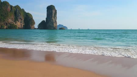 aonang : Relax on the picturesque Monkey beach with a view on the huge rock formation, gentle waves of Andaman sea and golden sand, Ao Nang, Krabi, Thailand Stock Footage