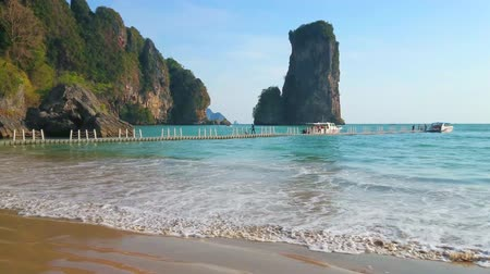 перевод : The tourists walk along the pontoon bridge to the speed boat, connecting small hidden  Monkey beach with Ao Nang town and Railay beach, Krabi, Thailand