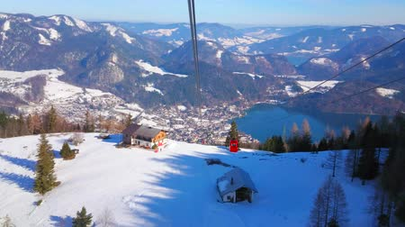 rüzgârla oluşan kar yığını : Watch the Alpine landscape of St Gilden and Wolfgangsee valley from the swinging gondola of Zwolferhorn cableway on the windy weather, Salzkammergut, Austria Stok Video