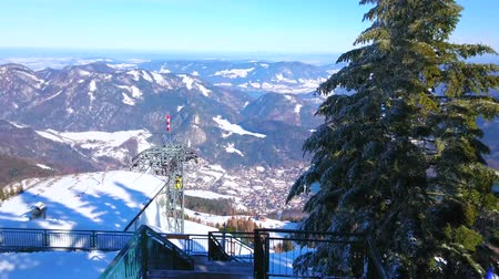 snowbound : The viewing terrace above the upper station of cableway of Zwolferhorn mount overlooks the riding vintage gondolas, winter Alpine scenery and tall spruce, St Gilden, Salzkammergut, Austria