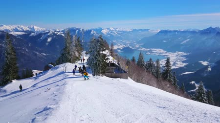 ski run : The snowy Zwolferhorn mountain peak with ski run, spruces on the slope and azure Wolfgangsee lake valley, seen on background in surrounding of Alpine range, Salzkammergut, Austria
