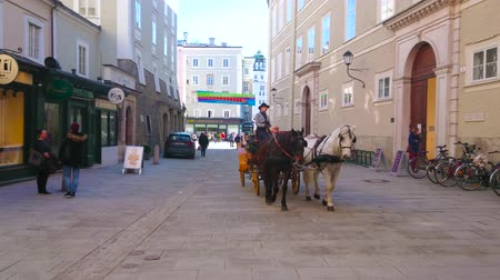 stragan : SALZBURG, AUSTRIA - FEBRUARY 27, 2019: Tourists enjoy the city tour in old style horse drawn carriage, riding along the old edifices of Churfurststrasse street of Old Town, on February 27 in Salzburg