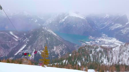 hegytömb : EBENSEE, AUSTRIA - FEBRUARY 24, 2019: The snowfall above the foggy Traunsee lake and valley, seen from the top of Feuerkogel mount with riding chairlift on the foreground, on february 24 in Ebensee