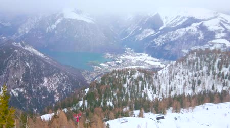 hegytömb : EBENSEE, AUSTRIA - FEBRUARY 24, 2019:  Watch misty Traunsee valley from the snowy slope of Feuerkogel mount with its chairlifts, pistes and pine forests on snowfall, on february 24 in Ebensee