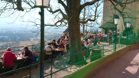 столовая гора : SALZBURG, AUSTRIA - FEBRUARY 27, 2019: The crowded sunny terrace of Hohensalzburg Castle with small tables and chairs of outdoor restaurant, on February 27 in Salzburg. Стоковые видеозаписи