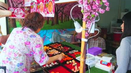 sudeste : BANGKOK, THAILAND - APRIL 22, 2019: The small outdoor sushi bar with variety of rolls to take away, located in Charkrapong Road, Banglampoo, on April 22 in Bangkok