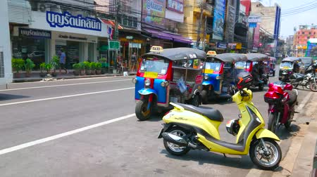 siamês : BANGKOK, THAILAND - APRIL 22, 2019: The slow traffic along the Charkrapong Road with parked tuk tuks and scooters, lined with shops and cafes of Banglampoo tourist district, on April 22 in Bangkok Stock Footage