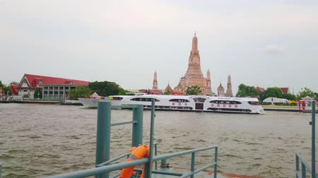 кхмерский : BANGKOK, THAILAND - APRIL 22, 2019: The luxury tourist ferry floats along the Wat Arun Temple on Chao Phraya river, on April 22 in Bangkok