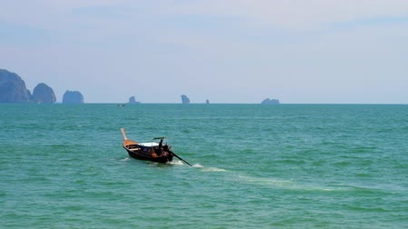 aonang : The Andaman seascape with old longtail boat, floating to the rocky islands, seen on horizon, Ao Nang, Krabi, Thailand Stock Footage