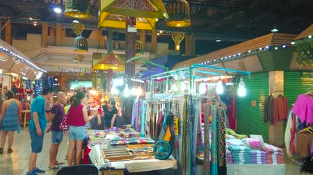 bazar : CHIANG MAI, THAILAND - MAY 2, 2019: People choose interesting pieces of clothes and accessories in stalls of Night Bazaar, on May 2 in Chiang Mai