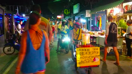 food court : PAI, THAILAND - MAY 5, 2019: The crowded Night Market in Walking Street with many food and souvenir stalls, cafes, bars; the street vendor with cart offers home made coconut ice cream, on May 5 in Pai Stock Footage