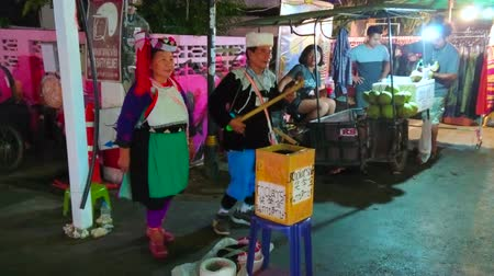 племя : PAI, THAILAND - MAY 5, 2019: The couple of senior members of Lisu Hill Tribe in traditional costumes sings and dances, playing tseubeu banjo-like musical instrument in Walking Street, on May 5 in Pai
