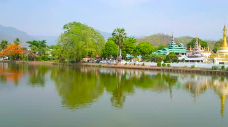sztúpa : The picturesque panorama of Nong Kham lake, lined with lush greenery of public park, Wat Chong Kham and Wat Chong Klang Burmese style temples, reflecting on the lakes surface, Mae Hong Son, Thailand