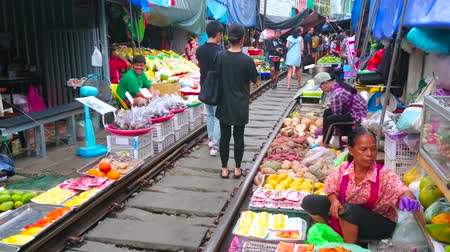 romênia : MAEKLONG, THAILAND - MAY 13, 2019: The tourists and visitors walk along the railroad of Maeklong Railway Market, make pictures and choose fresh fruits and other foods, on May 13 in Maeklong Stock Footage