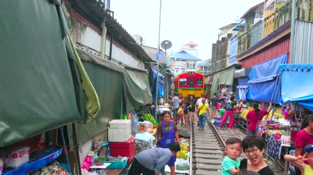 maeklong : MAEKLONG, THAILAND - MAY 13, 2019: The vendors spread out the sunshades, and tents, lay out their goods after the train had ridden along the railroad of Maeklong Railway Market, on May 13 in Maeklong Stock Footage