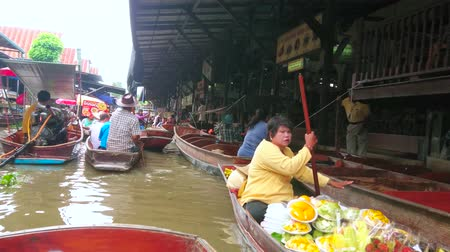 ratchaburi : DAMNOEN SADUAK, THAILAND - MAY 13, 2019: Make some shopping, choosing foods, fruits and souvenirs in sampans (boats) of Ton Khem floating market vendors, on May 13 in Damnoen Saduak Stock Footage