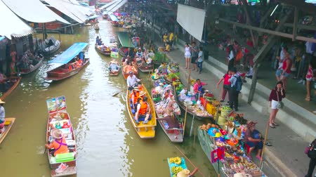 ratchaburi : DAMNOEN SADUAK, THAILAND - MAY 13, 2019: Chaotic boat traffic along klong (canal) of Ton Khem department of floating market with souvenirs, snacks, fruits and other goods, on May 13 in Damnoen Saduak