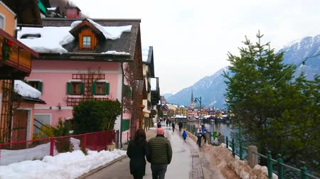 hegytömb : HALLSTATT, AUSTRIA - FEBRUARY 21, 2019: Enjoy the walk along Seestrasse  embankment of the winter town, facing Hallstatter see (lake) and rocky Alpine slopes of Dachstein, on February 21 in Hallstatt. Stock mozgókép