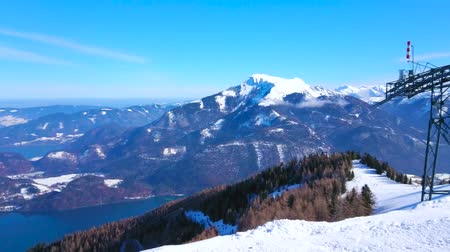 ski run : Watch the snowy Alpine scenery from the top of Zwolferhorn Mount with riding vintage gondolas of cable car and turquoise Wolfgangsee lake, seen in valley, St Gilden, Salzkammergut, Austria