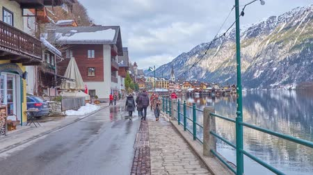 hallstatter see : HALLSTATT, AUSTRIA - FEBRUARY 25, 2019: Pleasant walk along embankment of Hallstatt with a view on line of traditional houses, old port, Hallstattersee lake and snowy Alps, on February 25 in Hallstatt