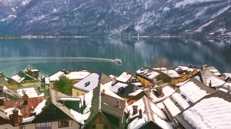hallstatter see : Enjoy the view on ferry, floating along Hallstattersee lake and leaving its wake on the calm water surface, from a viewpoint behind the city roofs, Salzkammergut, Austria. Stock Footage