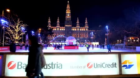 rathauspark : VIENNA, AUSTRIA - FEBRUARY 18, 2019: People enjoy their free time on ice skating rink in Rathaus square next to Town Hall (Rathaus) building, on February 18 in Vienna.