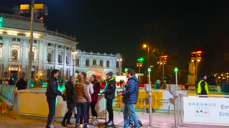 rathauspark : VIENNA, AUSTRIA - FEBRUARY 18, 2019: The crowded entryexit point of the Rathausplatz ice skating rink with a view on illuminated Burgtheater on background, on February 18 in Vienna. Stock Footage