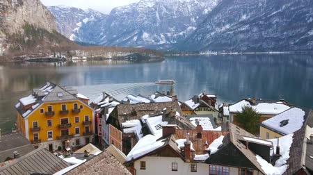 hallstatter see : The cityscape of old Hallstatt with a view on snowy roofs and floating ferry, leaving the long wake on crystal clear surface of Hallstattersee lake, Salzkammergut, Austria