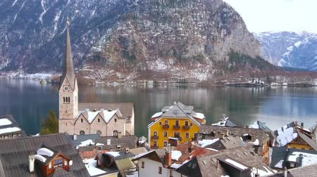 evangelical : The scenic cityscape of winter Hallstatt with snowy roofs of old townhouses, tall spire of Evangelical Kirche (church), calm surface of Hallstattersee lake and rocky slopes of Dachstein Alps, Austria