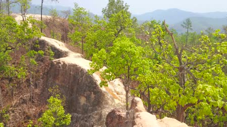 erozyon : Explore the Pai Canyon (Kong Lan) with its unique landscape, narrow and curved paths along the tall steep cliffs, green forest and yellow clay soil, Thailand Stok Video