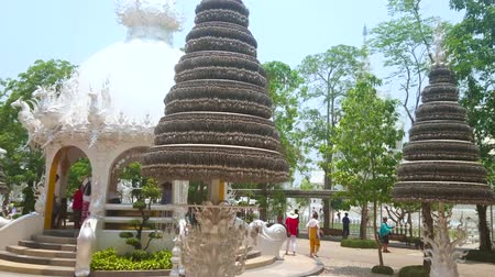 chiang rai : CHIANG RAI, THAILAND - MAY 9, 2019: The carved shrine and prayer trees with numerous metal bo (pho, bodhi) silver leaves, located on the grounds of White Temple (Wat Rongkhun), on May 9 in Chiang Rai Stock Footage
